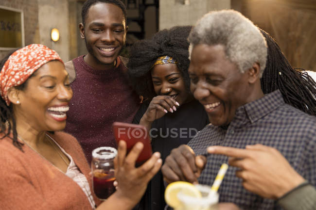 Happy multi-generation family laughing, using smart phone — Stock Photo