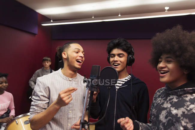 Smiling teenage boy musicians recording music, singing in sound booth — Stock Photo