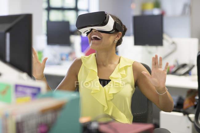 Donna di affari entusiasta utilizzando il simulatore di realtà virtuale vetri in ufficio — Foto stock
