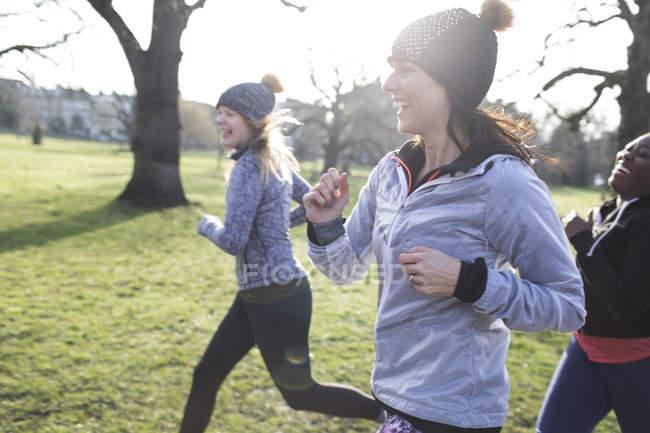 Corredoras sonrientes corriendo en el soleado parque - foto de stock