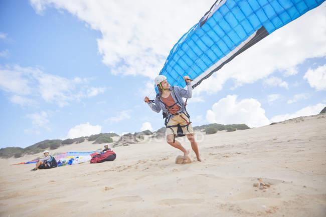 Parapente masculino executando com para-quedas na praia — Fotografia de Stock