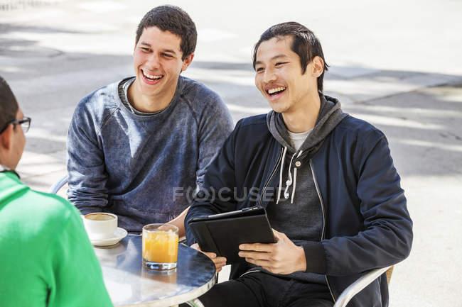 Männliche Freunde mit digitalem Tablet lachen über Bürgersteig-Café — Stockfoto