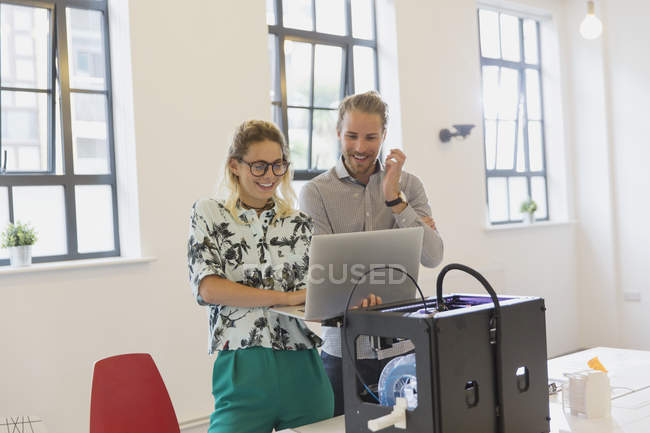 Designers using laptop at 3D printer in office — Stock Photo
