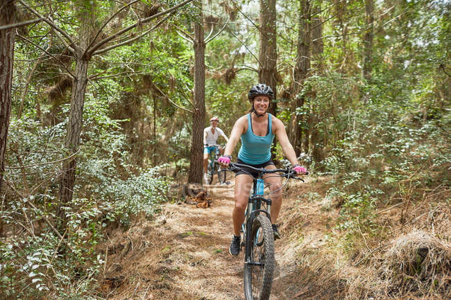 Carefree woman mountain biking on trail in woods — Stock Photo