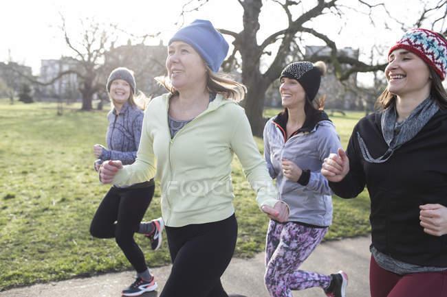Confident corridori femminili in esecuzione nel parco soleggiato — Foto stock
