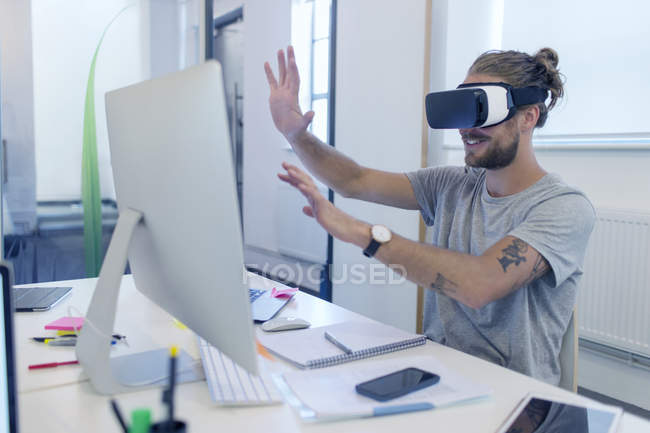 Male computer programmer programming virtual reality simulator glasses at computer in office — Stock Photo