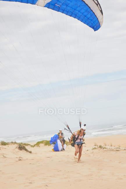 Feminino parapente com para-quedas na praia do oceano — Fotografia de Stock