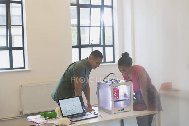 Designers regardant imprimante 3D dans le bureau — Photo de stock