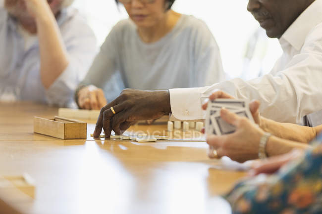 Senior friends playing games at table in community center — Stock Photo