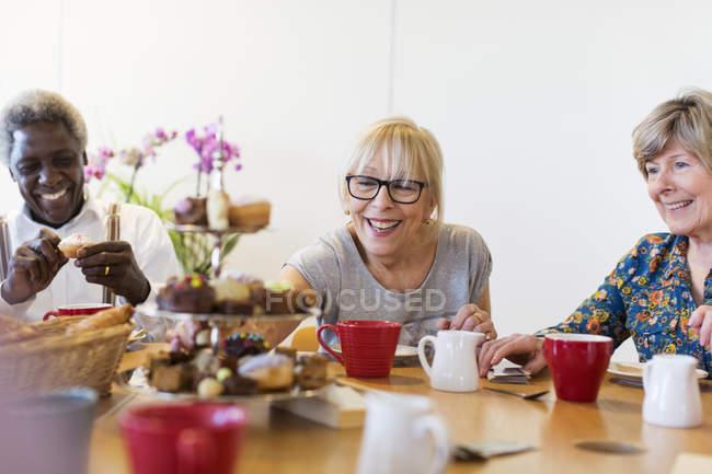 Amis aînés appréciant le thé et le dessert de l'après-midi dans le centre communautaire — Photo de stock