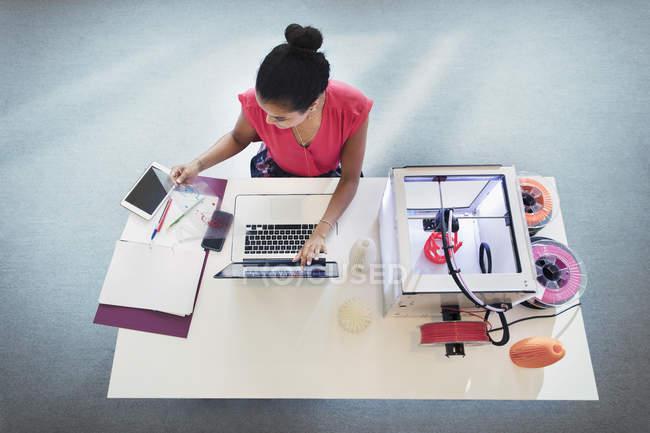 Diseñadora femenina en laptop junto a impresora 3D - foto de stock