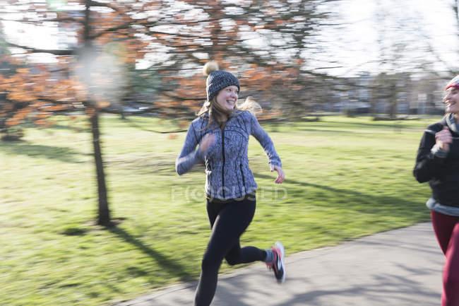 Посміхаючись, впевнена в собі жінка бігун працює в Сонячний парк — стокове фото