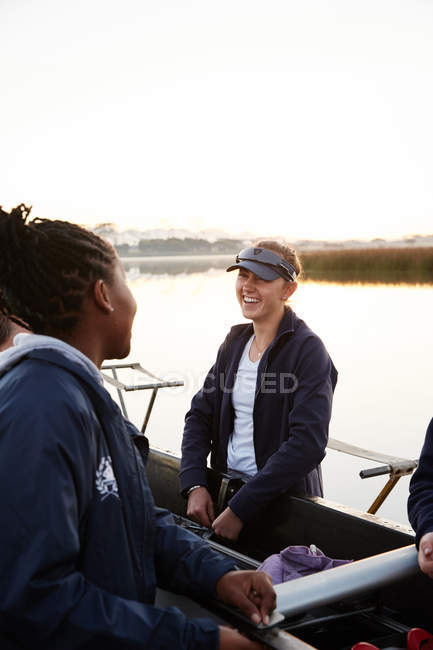 Female rowers talking, carrying scull — Stock Photo