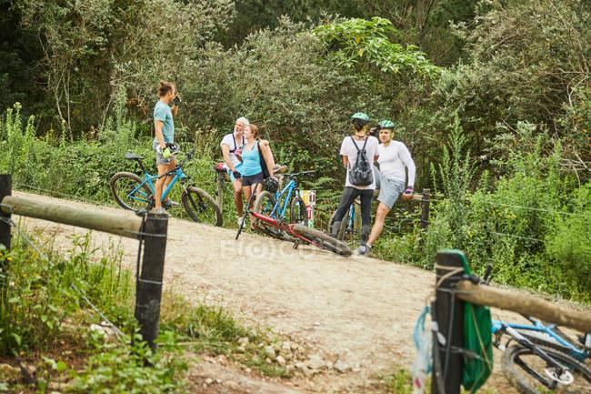 Friends mountain biking, resting on trail — Stock Photo