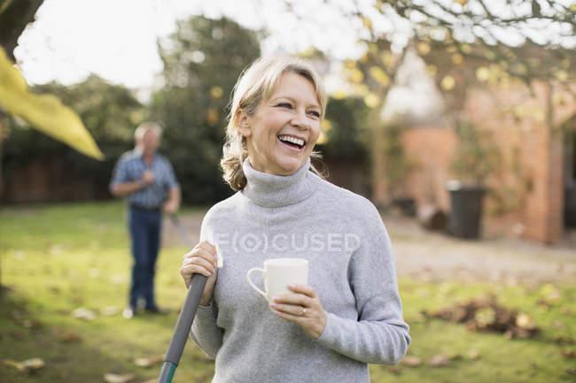 Portrait of blonde mature woman having coffee break in garden — Stock Photo