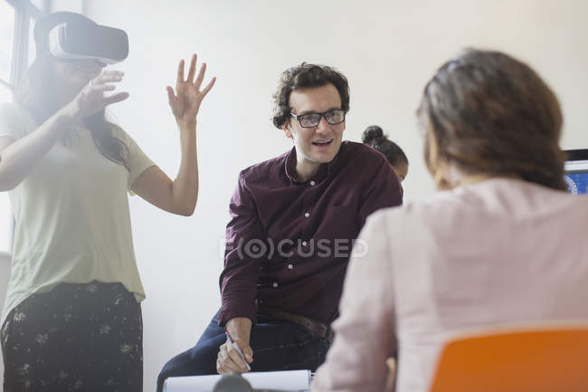 Computer programmers testing virtual reality simulator glasses in conference room meeting — Stock Photo