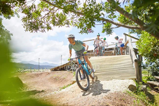 Человек горный велосипед вниз солнечной полосе препятствий рампы — стоковое фото