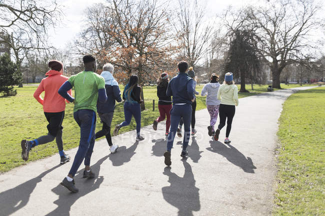 Group of runners running in sunny park — Stock Photo