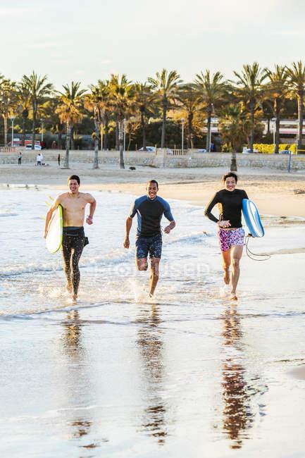 Surfeurs masculins enthousiastes s'exécute en surf sur la plage de l'océan — Photo de stock
