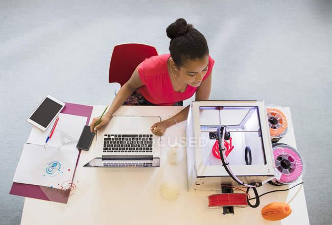 Diseñadora femenina en laptop viendo impresora 3D - foto de stock