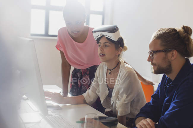 Computer programmers programming virtual reality simulator glasses at computer in office — Stock Photo
