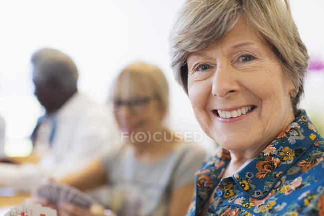 Retrato sorrindo, mulher sênior confiante jogando cartas com amigos — Fotografia de Stock