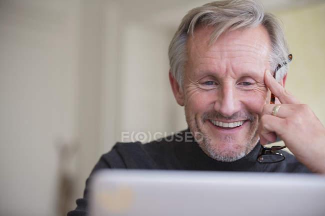 Souriant homme mature pigiste travaillant à l'ordinateur portable — Photo de stock