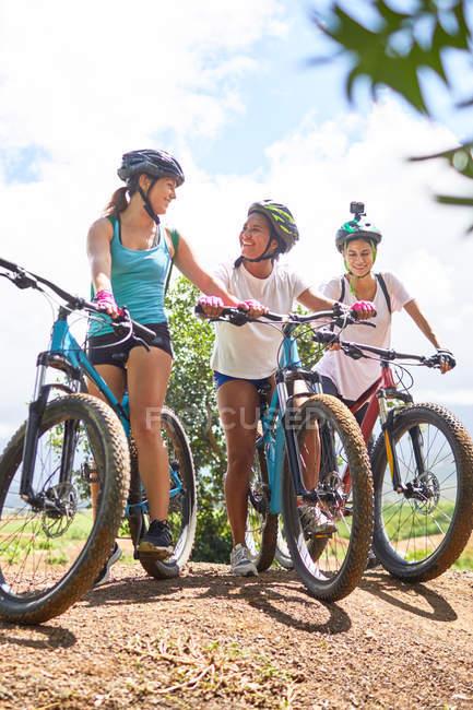 Women friends mountain biking on sunny trail — Stock Photo