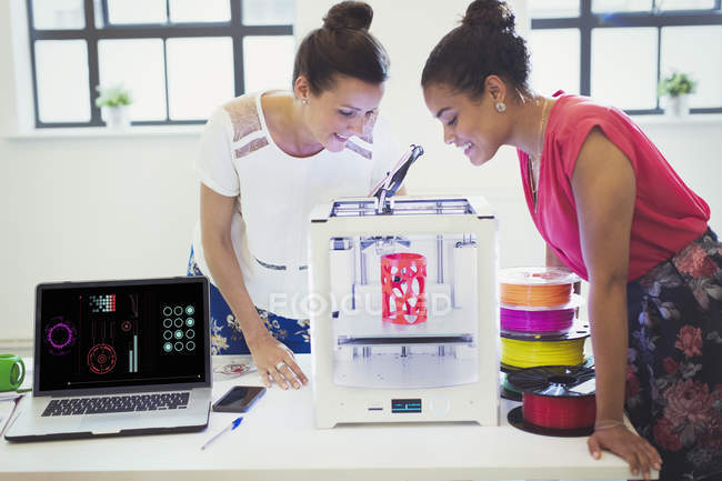 Designers féminins regardant imprimante 3D dans le bureau — Photo de stock