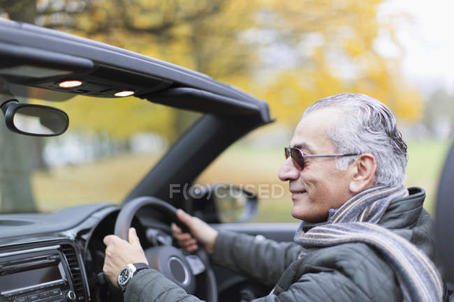 Senior man driving convertible car — Stock Photo