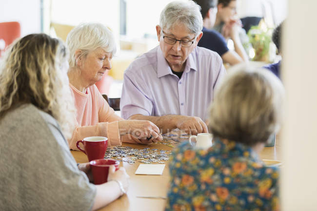 Senior friends assembling jigsaw puzzle and drinking tea at table in community center — Stock Photo