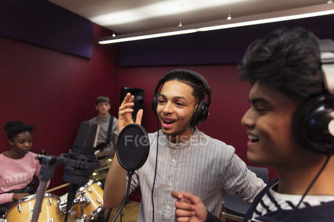 Teenage musicians recording music in sound booth — Stock Photo