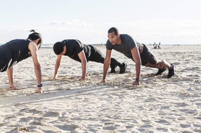 Мужчины отжимаются на солнечном пляже — стоковое фото