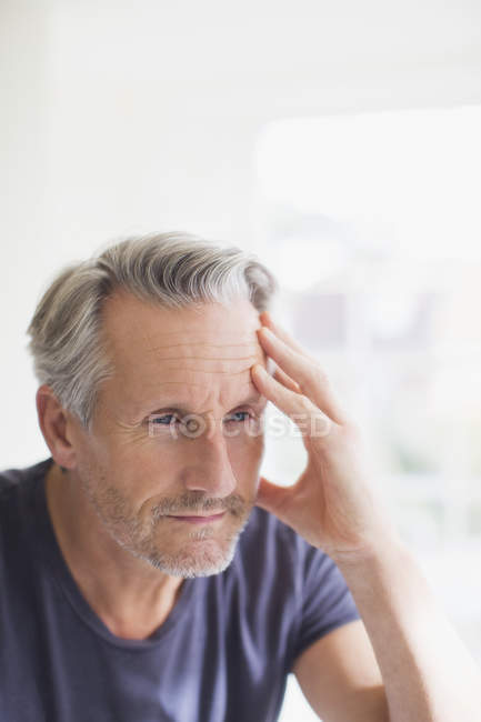Tired mature man holding head in hand at bathroom mirror — Stock Photo