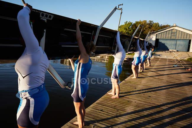 Weibliche Ruderer heben Schädel am sonnigen Seeufer dock — Stockfoto