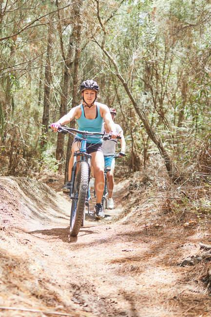 Woman mountain biking on sunny trail in woods — Stock Photo