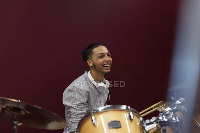 Happy teenage boy musician playing drums in sound booth — Stock Photo