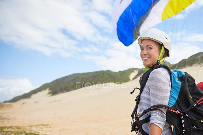 Retrato sorridente, confiante jovem parapente feminino na praia — Fotografia de Stock