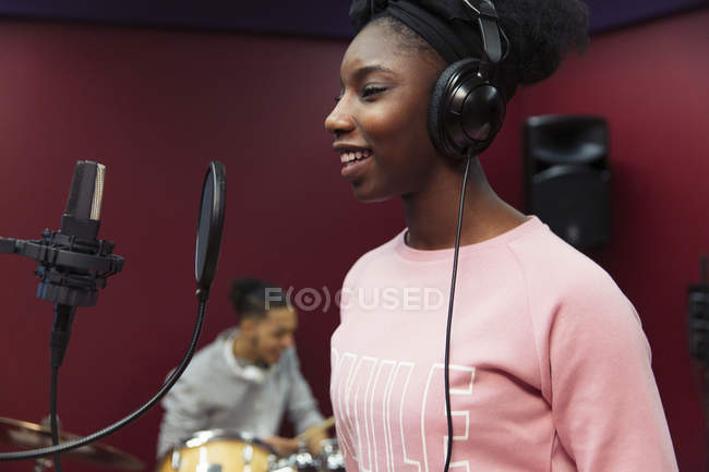 Smiling teenage girl musician recording music, singing in sound booth — Stock Photo