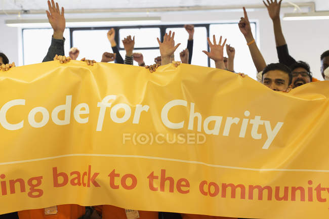 Хакеры со знаменами аплодируют, кодируют для благотворительности на хакатоне — стоковое фото