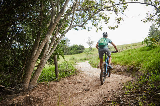 Man mountain biking on rural trail — Stock Photo