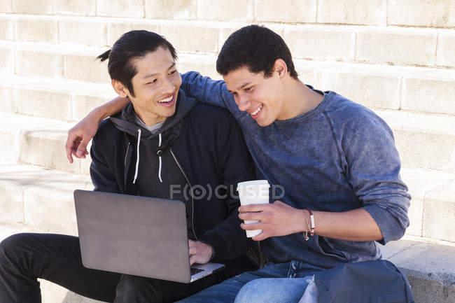 Maschio gay coppia utilizzando laptop e bere caffè — Foto stock