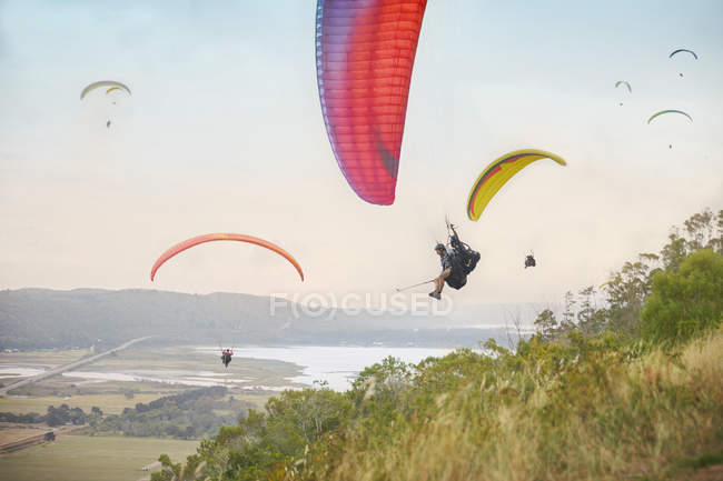 Paragliders in sky over landscape — Stock Photo