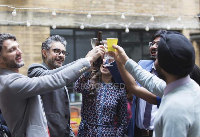 Amigos brindando cerveja e coquetéis na festa no pátio — Fotografia de Stock