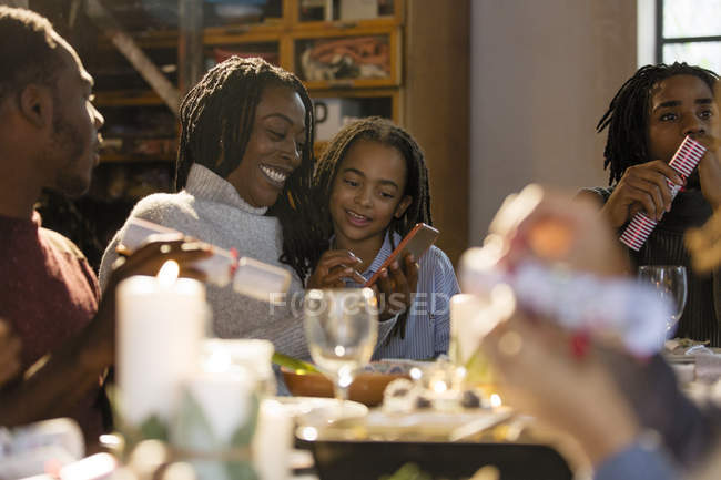 Mother and daughter using smart phone at Christmas dinner — Stock Photo