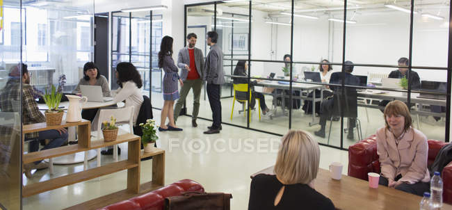 Creative business people talking in open plan office — Stock Photo