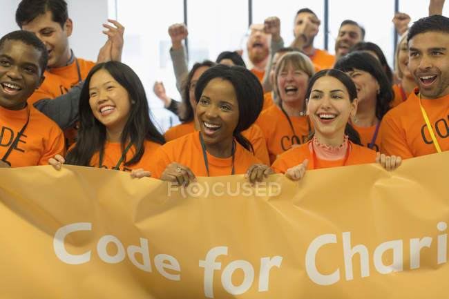 Happy hackers with banner coding for charity at hackathon — Stock Photo