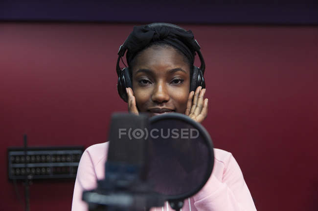Portrait confident teenage girl musician recording music, singing in sound booth — Stock Photo