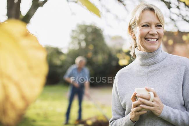 Retrato de mujer madura rubia tomando un café en el jardín - foto de stock