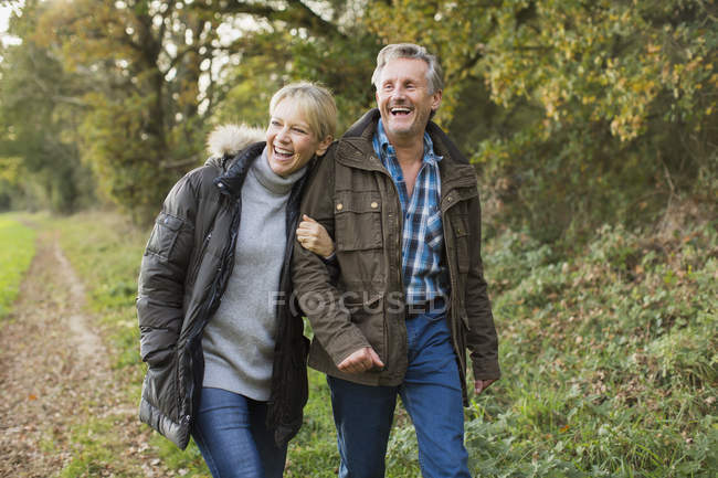 Pareja caucásica madura caminando juntos en el parque de otoño - foto de stock